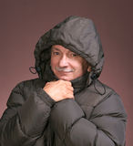 Winter man. Close-up portrait of a senior man in winter clothing on a brown background royalty free stock photos