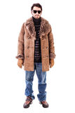 Winter man. A cheerful young man wearing an expensive sheepskin furry coat isolated over a white background Royalty Free Stock Photos