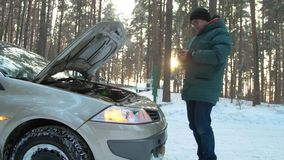 In winter, a man repairs a broken car. A man stands at the open hood of car and is looking for breakage. In winter, a man repairs a broken car. Side view. A man stock video