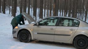 In winter, a man repairs a broken car. A man stands at the open hood of car and is looking for breakage. In winter, a man repairs a broken car. Side view. A man stock footage