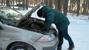 In winter, a man repairs a broken car. A man stands at the open hood of car and is looking for breakage. In winter, a man repairs a broken car. Side view. A man stock video footage