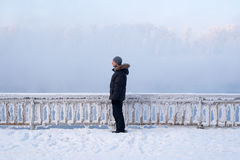 Winter man standing in front of the fence Stock Images