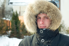 Winter - man in warm jacket with furry hood. In the yard Stock Image
