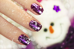 Winter manicure. Christmas new year winter manicure with the design of the white snowflakes on violet brilliant varnish for the nails on the background of the Royalty Free Stock Images