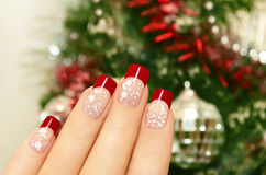 Winter manicure. Winter manicure with red lacquer and white chips on the background of the Christmas tree Stock Photo