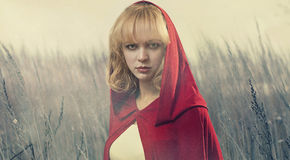 Winter meadow view. Young woman in red cape at winter snowy meadow Royalty Free Stock Photo