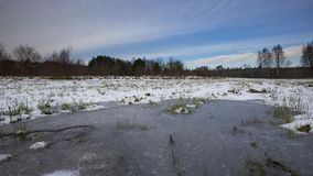 Winter meadows with snow and frozen puddle Stock Photography