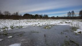 Winter meadows with snow and frozen puddle Stock Image