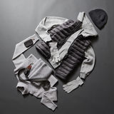 Winter men's clothes and accessories. On a black background. Winter sweater, gloves, jacket, belt, hat and purse Stock Photography