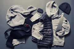 Winter men's clothes and accessories. Collection of men's warm clothes on a dark background. Winter sweater, gloves, jacket, belt, hat, saw and purse Stock Photos