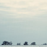 Winter minimalist landscape. The field is covered with snow on t Royalty Free Stock Photos