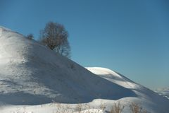 Winter minimalistic landscape of a snow-capped hill on which a lonely tree stands against a blue sky on the shady side Stock Photo