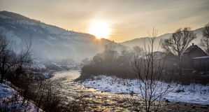 Winter mist landscape with mountains, river and houses Royalty Free Stock Images