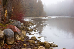 Winter mist on northern river. Early freeze on Canadian river with colored rocks Royalty Free Stock Photos