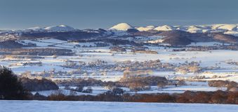 Panoramic view over Hilly British Countryside in Snow. Winter mist streching over scenic panorama of Shropshire Hills in snow, UK Stock Images