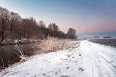 Winter misty dawn on the river. Rural foggy and frosty scene. Stock Photo