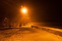 Winter misty embankment in the light of lanterns.  stock photos