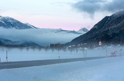 Winter misty road and village Royalty Free Stock Photography