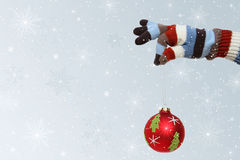Winter mitten with Christmas ball. Winter mitten holding a Christmas ball stock photos