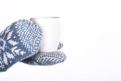 Winter Mittens and Hot Mug. Hands in a pair of blue and white knit winter mittens holding a hot cup of coffee, tea or hot cocoa Royalty Free Stock Photos