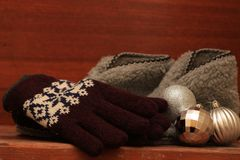 Winter mittens, warm slippers and silver Christmas balls. On a wooden table stock photos