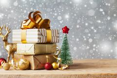 Winter mockup with Christmas gift or present boxes and holiday decorations on wooden background. Greeting card with snow effect. stock photography