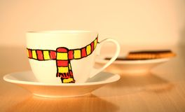 Winter mood in coffee cup. S. A porcelain coffee cup with a funny scarf pattern hand-painted on it giving a comfy mood for a cold winter evening Stock Photos