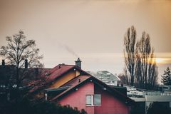 Building roofs, naked trees, sunset, fog over the lake Royalty Free Stock Photos