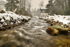 Winter mood. A river flowing from the mountains around the old mill Royalty Free Stock Image