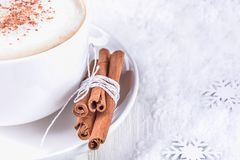 Winter mood. White cup of coffee cappuccino with cinnamon on a white wooden background. Winter coffee. White cup of coffee cappuccino with cinnamon on a white stock photography