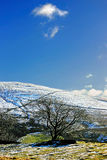 Winter Moorland - Yorkshire UK. Snow-covered moorland hills beneath a blue winter sky in Yorkshire UK Stock Image