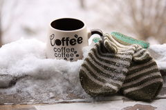 Winter morning. A cup of coffee in winter morning in windowsill covered with snow with green mittens Royalty Free Stock Photography