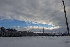 The winter morning in the countryside. Winter morning in the countryside, the sun illuminates the sky in different colors, all covered with snow, the field is royalty free stock photos
