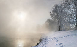 Winter morning on the river. Winter landscape misty morning on the river at sunrise Stock Images