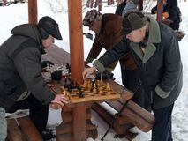 Winter 2016, Moscow, Russia. Elderly people playing chess outdoors. Winter 2016, Moscow, Russia. Older people play chess outdoors in winter city Park stock images