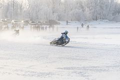 Winter motocross, Driver with motorcycle. Race. Winter Speedway. Motorcyclists unmarked go on a winter road entering in dangerous turn stock images