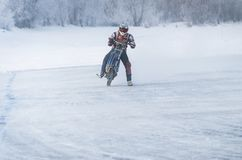 Winter motocross, Driver with motorcycle. Race Winter Speedway. rider ekstremal raised the bike on the rear wheel royalty free stock photo