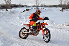 Winter motocross racer on a motorcycle rides in turn of Royalty Free Stock Images