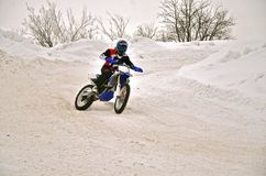Winter motocross racer on a motorcycle turns with the slope and Stock Photography