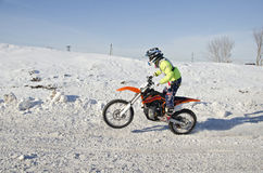 Winter Motocross racer rides standing up on the rear wheel Stock Images