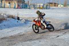 Winter motocross, rider on bike is accelerating. Winter motocross, the rider on the motorcycle is accelerating at the exit of a turn on a snow track, with a Stock Photo