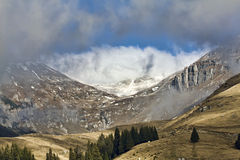 Winter mountain. Valley and mountain peak, with blue sky and clouds Stock Photos