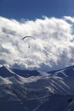 Winter mountain with clouds and silhouette of parachutist Stock Image