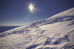 Winter mountain covered with snow against the sun Stock Photography