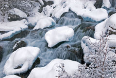 Winter mountain creek cascades and snowfall Stock Photos