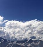 Winter mountain in evening and sunlight silhouette of parachutis Stock Photos