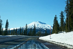 Winter Mountain Highway To Mt. Bachelor. The snowy winter Cascade Lakes Highway with Mt. Bachelor, Oregon ski resort in the background stock image