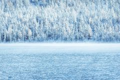 Winter mountain lake with snow-covered pine trees on the shore. Frosty weather, fog over the winter lake, a sharp decrease in temperature. A number of snow Royalty Free Stock Photography