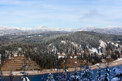 Winter Mountain Landscape. A winter landscape taken from a high elevation of tree tops, lake water, a highway, and large snow covered mountains in Northern Idaho Royalty Free Stock Images