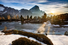 Winter mountain landscape with frozen lake in the front Royalty Free Stock Photo